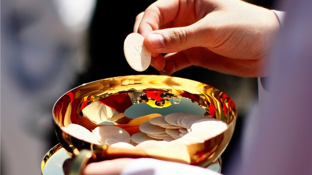 A priest holds a Holy Communion wafer