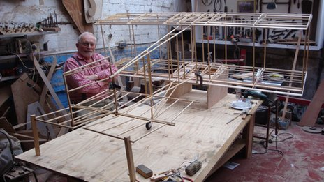 Merlin Maddock in his workshop with a scale model of Carlyon's glider