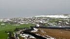 A panoramic view of some snow in fields and over houses.