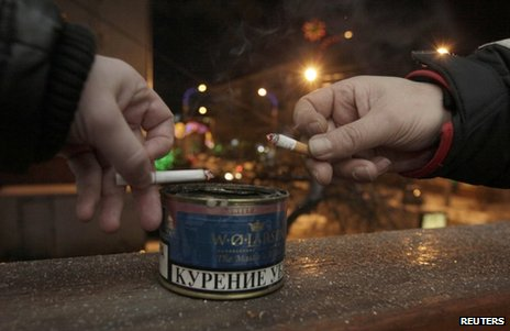 Men drop ash in a tin while smoking on the balcony of an office building in Krasnoyarsk, Russia, 24 January