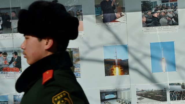 A Chinese policeman marches past photos of North Korea&#039;s recent rocket launch outside the North Korean embassy in Beijing 