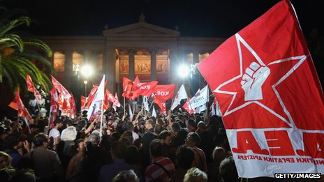 (File photo) Syriza party members wave flags outside a rally