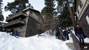 Members of the news media are shown outside a home, at left, in Big Bear, California, where two women were taken hostage by fugitive Christopher Dorner