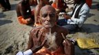 Hindu holy man gets his beard shaved