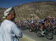 An Omani man watches cyclists 