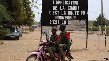 Malian soldiers on a motorcycle by a Sharia sign - 12 February 2013 