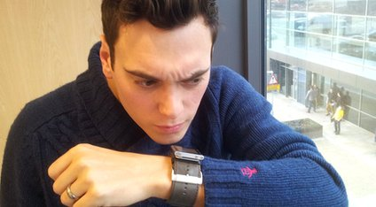 Joe speaking into his watch
