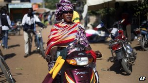 A woman in colourful dress on a motorbike in Gao, Mali - 30 January 2013