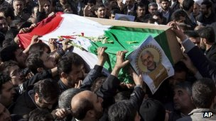 Iranian mourners carry the flag draped coffin of Gen Hassan Shateri, in Tehran, Iran