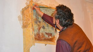 Museum staff restore a wall painting from King Herod's palace