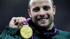 Oscar Pistorius holds a gold medal after his Olympic win.
