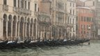 Venice gondolas lined up in front of buildings. Snow falling quickly across the whole picture.