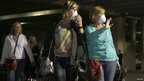Passengers leave the Carnival Triumph cruise ship after reaching the port of Mobile, Alabama, on 14 February 2013