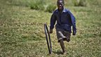 A Kenya boy playing with a bicycle tyre in a camp for displaced people - Sunday 10 February 2013