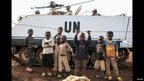 Children in front of a UN tank, on holding onto a piece of barbed wire, Bukavu, DR Congo - Thursday 14 February 2013