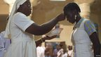 A Catholic nun marks a woman's head with ash in Bamako's cathedral, Mali - Wednesday 13 February 2013