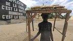 A baker with a table of bread on his head, behind him a sign declaring Sharia in Gao, Mali - Tuesday 12 February 2013