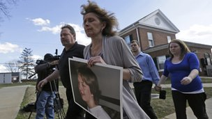 Kim Scruggs carries a picture of her son as she arrives for a hearing in Appottamox County, Virginia 15 February 2013