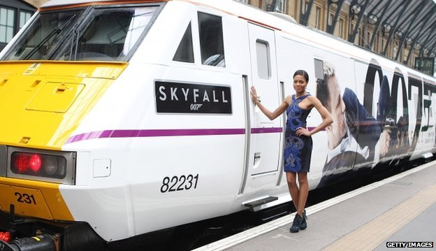 Bond girl Naomie Harris stands next to the train