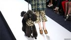 A model walks with a poodle as she presents a creation by Mulberry during the 2013 Autumn/Winter London Fashion Week in London