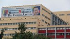 A banner showing Venezuelan President Hugo Chavez hangs outside the hospital where he is being treated on his return to Caracas, 18 Feb 2013