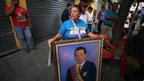A woman holds a portrait of Hugo Chavez near Bolivar Square, Caracas (18 Feb 2013)