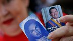 A supporter holds pictures of Jesus Christ and Venezuela President Hugo Chavez in Caracas, 18 Feb 2013