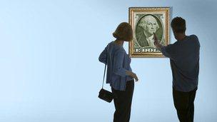 Couple examines a framed dollar bill