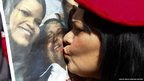 A supporter of Hugo Chavez kisses a picture of him