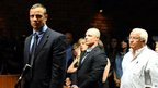 Oscar Pistorius in court with his brother Carl and father Henke behind him