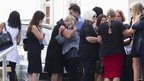 Reeva Steenkamp's mother June (centre, in grey) is comforted after her daughter's funeral service in Port Elizabeth