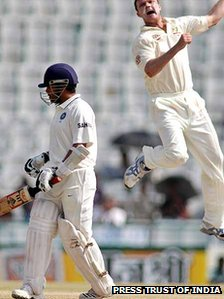 Australia's Doug Bollinger, right, jumps to celebrate the dismissal of Sachin Tendulkar, during the final day of their first cricket test match in Mohali. Chasing 216 to win, India were 162 for eight wickets in their second innings at lunch.