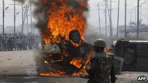 An Indian policeman looks on near a burning car during a trade union strike in Nodia on the outskirts of New Delhi on February 20, 2013