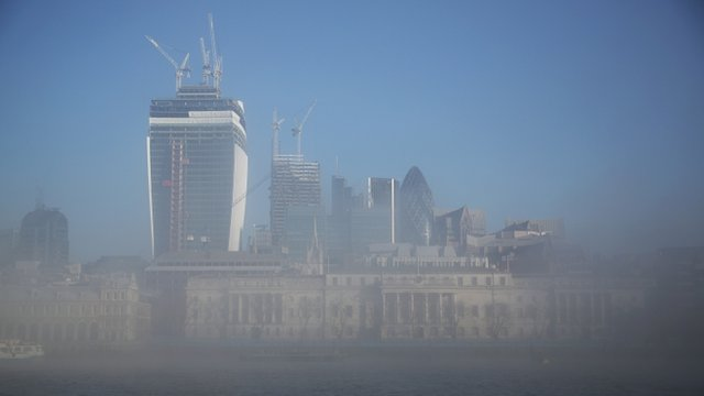 The City of London financial district emerges from early morning fog