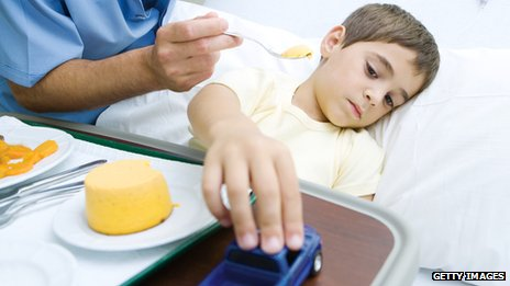 Nurse trying to feed sick child in hospital bed