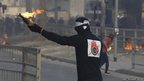 A protester holding a Molotov cocktail