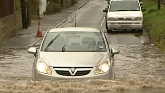 Cars negotiate deep floodwater in south-east England in December 2012