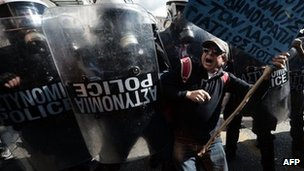 A demonstrator tries to pass a riot police cordon during a strike in Athens (20 Feb 2013)