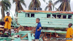 Children among debris of their storm-damaged school in 2004