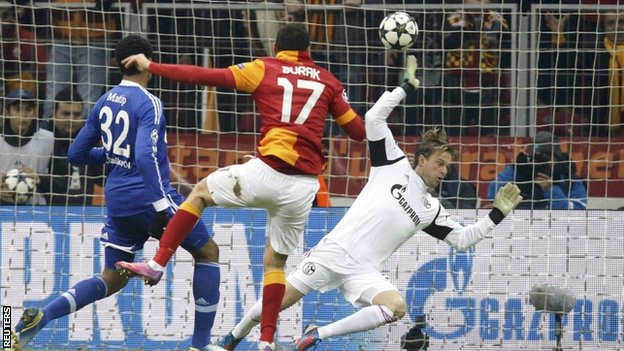 Galatasaray's Burak Yilmaz (c) scores past by Schalke 04's goalkeeper Timo Hildebrand