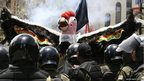 A man dressed as a condor faces Bolivian riot police