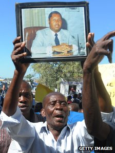 Man holding up a photo Jean-Claude Duvalier in office