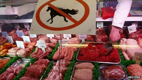 A butcher works behind a &quot;no horsemeat&quot; sign at Bates Butchers in Market Harborough, central England