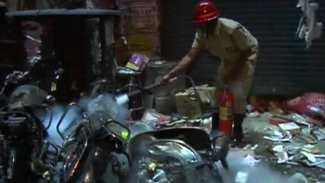 Hyderabad official extinguishing smouldering bicycles and motorbikes