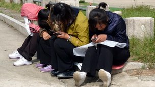 Girls on mobiles in a park in North Korea