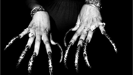 A woman's hands, with incredibly long painted nails