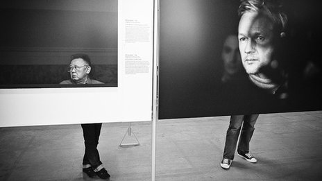 Two people stand behind images of Kim Jong-il and Julian Assange, with their legs appearing connecting to the large heads