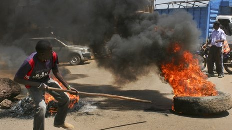 A protester prods a burning tyre roadblock as he and others take to the streets to protest the results of the Orange Democratic Movement (ODM) primary elections in Kisumu in January 2013