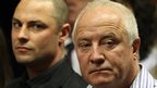 Oscar Pistorius' father Henke, right, and brother Carl watch as Oscar Pistorius arrives for his bail hearing at the magistrate's court in Pretoria, South Africa, 22 February 2013