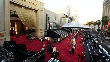 People prepare the red carpet at the Dolby Theatre for the 85th Academy Awards